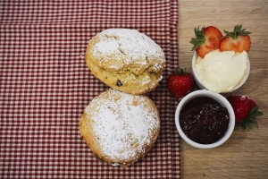 A picture of two scones with two pots of cream and jam