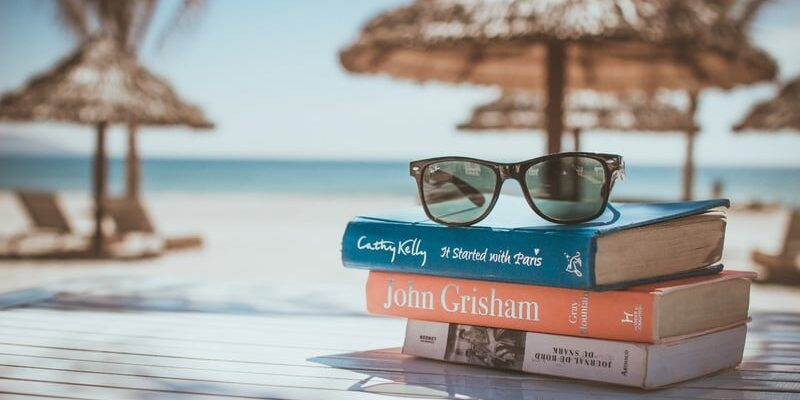 A picture of a beach with a table that has books and sunglasses on it