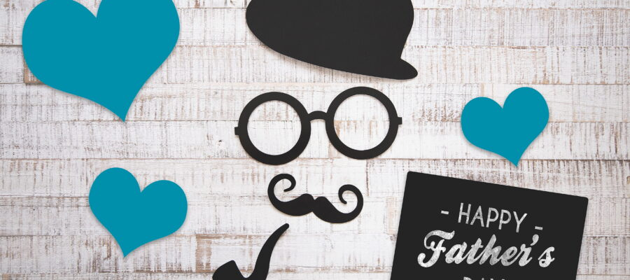 An image of a hat, glasses, moustache and smoking pipe cut out from paper on a background, for father's day